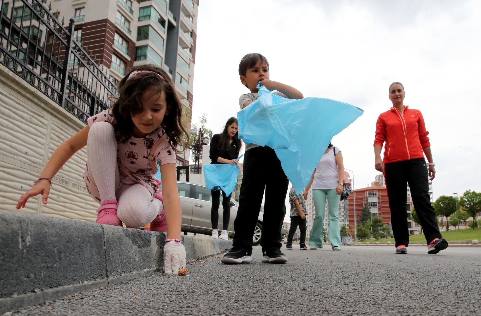 Anneler, çocuklarıyla parklardaki atıkları topluyor